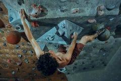 Hombre joven del escalador libre que sube el canto rodado artificial dentro fotografía de archivo libre de regalías
