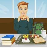 Hombre joven del estudiante que almuerza en restaurante de los alimentos de preparación rápida Imagen de archivo