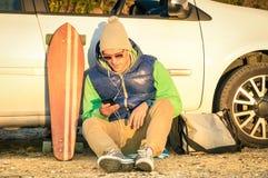 Hombre joven del inconformista con el smartphone que sienta después su coche Fotografía de archivo