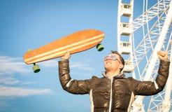 Hombre joven del inconformista con el tablero del patín del longboard en Luna Park Imagenes de archivo