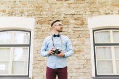 Hombre joven del inconformista con la cámara de la película en ciudad Foto de archivo
