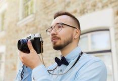 Hombre joven del inconformista con la cámara de la película en ciudad Fotografía de archivo