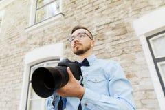 Hombre joven del inconformista con la cámara digital en ciudad Imágenes de archivo libres de regalías