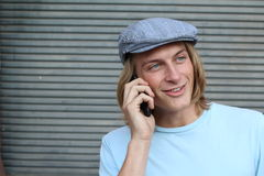 Hombre joven del inconformista hermoso en el sombrero que se coloca y que habla en el teléfono móvil Imágenes de archivo libres de regalías