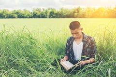 Hombre joven del inconformista que se sienta en el libro de lectura del prado con la naturaleza Imagen de archivo