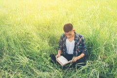 Hombre joven del inconformista que se sienta en el libro de lectura del prado con la naturaleza Fotografía de archivo