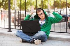 Hombre joven del inconformista que usa el ordenador portátil en calle de la ciudad Fotografía de archivo libre de regalías