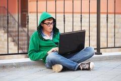 Hombre joven del inconformista que usa el ordenador portátil en calle de la ciudad Imagen de archivo libre de regalías