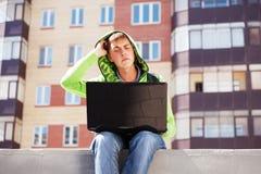 Hombre joven del inconformista que usa el ordenador portátil en calle de la ciudad Foto de archivo libre de regalías