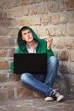 Hombre joven del inconformista que usa el ordenador portátil en los pasos Foto de archivo libre de regalías