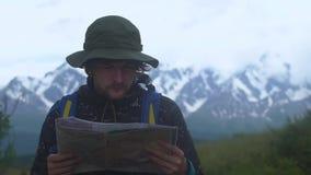 Hombre joven del inconformista triste con la mochila que se sostiene en manos y que mira en mapa de la montaña de niebla, caminan metrajes