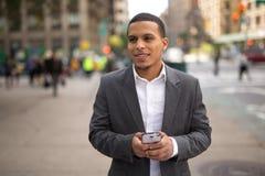Hombre joven del Latino en la ciudad que manda un SMS en el teléfono celular Imagenes de archivo