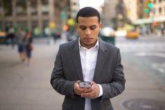 Hombre joven del Latino en la ciudad que manda un SMS en el teléfono celular Foto de archivo