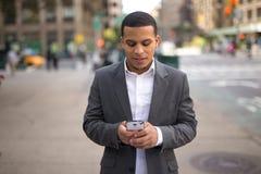 Hombre joven del Latino en la ciudad que manda un SMS en el teléfono celular Fotos de archivo