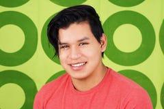 Hombre joven del latino que sonríe sobre verde Foto de archivo