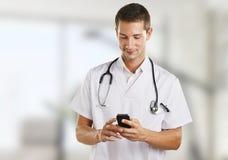 Hombre joven del médico con el estetoscopio que envía un mensaje en el hospital. Imagen de archivo