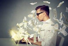 Hombre joven del perfil lateral que usa un ordenador portátil que hace el dinero Imágenes de archivo libres de regalías