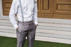 Hombre joven del primer en la camisa blanca y el pantalón gris de la escoria, con la mano en el bolsillo fotos de archivo libres de regalías