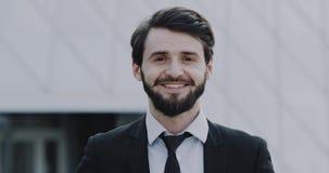 Hombre joven del primer en un traje con pan elegante que sonríe delante de la cámara 4K almacen de metraje de vídeo