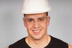 Hombre joven del retrato en un casco protector Fotos de archivo