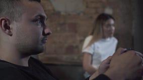 Hombre joven del retrato del primer que juega al videojuego que se sienta en el sofá en el cuarto del estilo del desván con la mu almacen de metraje de vídeo
