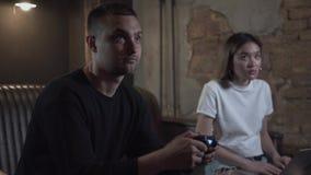 Hombre joven del retrato que juega al videojuego que se sienta en el sofá en el cuarto del estilo del desván con la muchacha smil metrajes