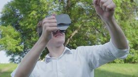 Hombre joven del retrato que lleva las auriculares de la realidad virtual que juegan al videojuego que disfruta de la imagen real almacen de video