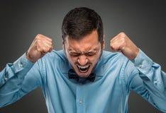 Hombre joven del trastorno enojado del retrato en la camisa azul, lazo de mariposa Fotos de archivo