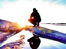 Hombre joven del viajero en la puesta del sol Turista que se sienta en el acantilado sobre el lago fotos de archivo