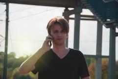 Hombre joven del viajero que habla a trav?s del tel?fono en el ferrocarril durante el tiempo caliente del verano, haciendo gestos fotos de archivo libres de regalías