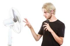 Hombre joven delante del ventilador Imagenes de archivo