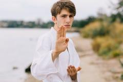 Hombre joven deportivo en el entrenamiento del karate del aire libre Muchacho en kimono en un fondo natural Ejercicio de concepto Foto de archivo libre de regalías