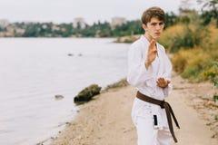 Hombre joven deportivo en el entrenamiento del karate del aire libre Muchacho en kimono en un fondo natural Ejercicio de concepto Fotos de archivo