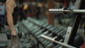Hombre joven deportivo que hace la pesa de gimnasia elevación-UPS en el gimnasio, resolviéndose para el cuerpo ideal metrajes