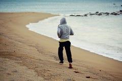 Hombre joven deportivo que se resuelve en la madrugada mientras que está corrido a lo largo de la costa sobre la arena mojada Imágenes de archivo libres de regalías