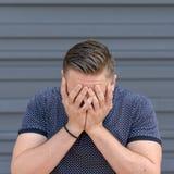 Hombre joven deprimido con su cabeza en sus manos fotografía de archivo
