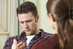 Hombre joven deprimido que habla con el consejero Fotografía de archivo