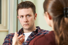 Hombre joven deprimido que habla con el consejero imágenes de archivo libres de regalías