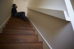Hombre joven deprimido que se sienta en las escaleras en casa Imágenes de archivo libres de regalías