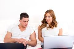 Hombre joven deprimido y chocado que mira el ordenador de la mujer Imagen de archivo libre de regalías