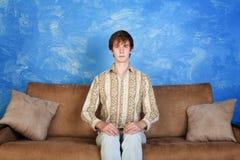 Hombre joven derecho en el sofá imagen de archivo libre de regalías