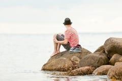Hombre joven descalzo de moda que se sienta en una roca Imagenes de archivo