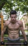 Hombre joven descamisado hermoso que ejercita en gimnasio al aire libre en parque foto de archivo libre de regalías