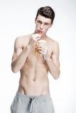 Hombre joven descamisado que bebe el zumo de naranja Foto de archivo
