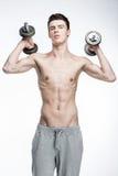 Hombre joven descamisado que lleva a cabo pesas de gimnasia Imágenes de archivo libres de regalías
