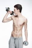 Hombre joven descamisado que lleva a cabo pesas de gimnasia Fotos de archivo