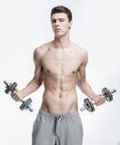 Hombre joven descamisado que lleva a cabo pesas de gimnasia Fotografía de archivo libre de regalías