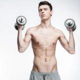 Hombre joven descamisado que lleva a cabo pesas de gimnasia Fotografía de archivo