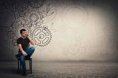Hombre joven desconcertado que se sienta en la silla que habla en su smartphone, individuo serio difícilmente de pensamiento con  foto de archivo