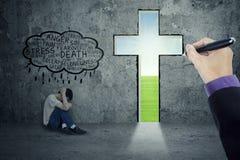 Hombre joven desesperado con una cruz Imagen de archivo libre de regalías